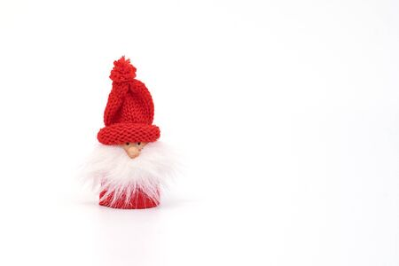 Miniature gnome or Santa in red hat and with fluffy beard isolated on white. Christmas and New Year greeting card with copy space