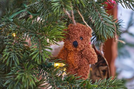 Small ornamental toy bear hanging on Christmas tree branch, close up view. Christmas decoration concept Stock fotó