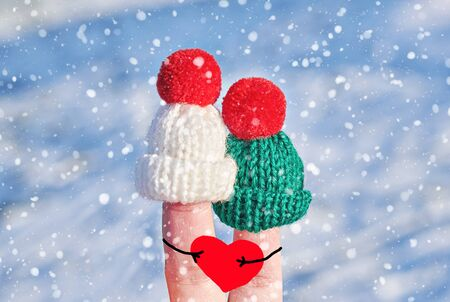 Funny couple fingers in knitted woolen hats with big red hearts in hands on blue winter background. Happy Valentines day or family celebrating concept Stock fotó