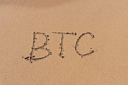 Letters BTC hand written at sandy beach. Unstable rise and fall of bitcoin concept, top view Stock fotó - 136787146