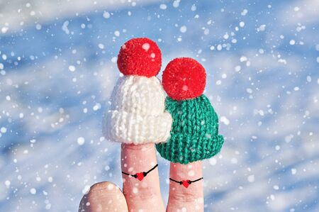 Funny couple fingers in knitted woolen hats with hearts in holding hands on blue winter background. Happy Valentines day or family celebrating concept Stock fotó