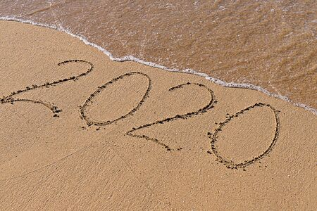 Numbers 2020 hand written at sandy seashore beach. Lettering with 2020 for celebrating New Year. Happy new year symbol. Abstract art Stock fotó
