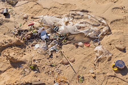 Discarded garbage by wave at beach, cigarette butt, plastic packaging and bottle cork at sandy shore, close up view. Global oceans pollution concept Stock fotó - 136788108