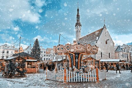 View of old Tallinn central square during Christmas market. Vintage carousel, Christmas tree and kiosks illuminated with Xmas light and walking crowd Stock fotó