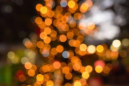 Yellow bokeh on black background. Abstract blur gold sparkle bokeh. Garland light bulb blur light bokeh. Glow light effect. Christmas holiday pattern