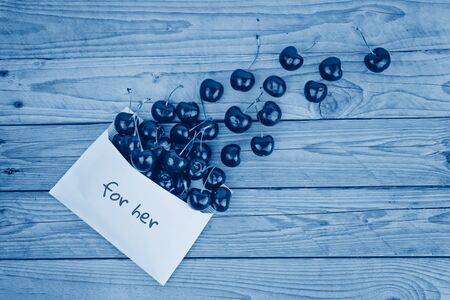 Ripe cherries dropped from white envelope. Valentines day greeting card concept, toned classic blue color