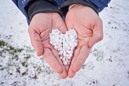 Closeup view of mens hands hold snow in shape of heart in palms. Wntertime leisure activity concept Stock fotó - 136788152