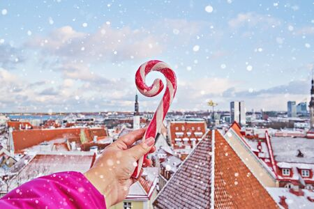 Striped candy cane lollipop in hand against old city of Tallinn. Iconic view of Tallinn old cityscape skyline from observation deck. Christmas travel concept Stock fotó - 136788330