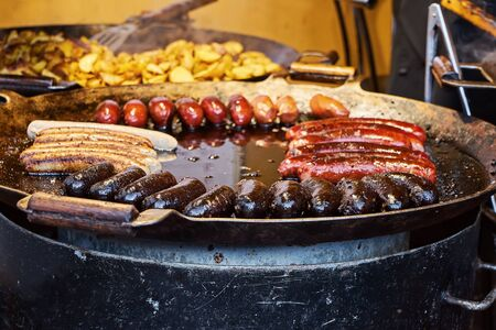 Closeup view of pan with hot sausages with potato for sale during Christmas market. Traditional Xmas street food in Baltic