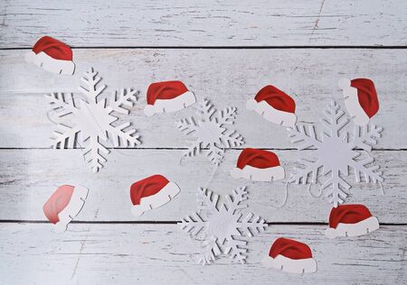 Santas paper-cut hats and paper snowflakes on wooden background, flat lay. Abstract handmade craft Christmas background Stock fotó