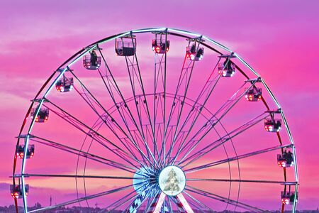 Closeup colorful Ferris wheel against sunset pink sky. Abstract cityscape view, motion blur, selective focus