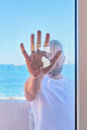 Caucasian man with raised hand through window glass. Problem of social domestic violence concept Stock fotó