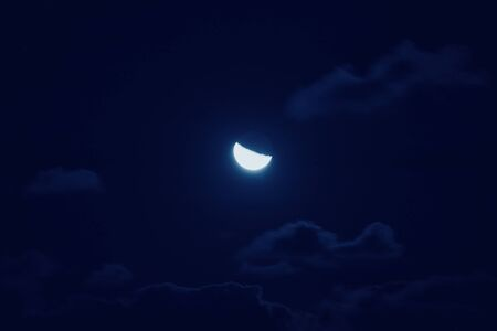 Half of bright moon among dark clouds in night sky with motion blur. Moon gathering concept Stock fotó - 136253360