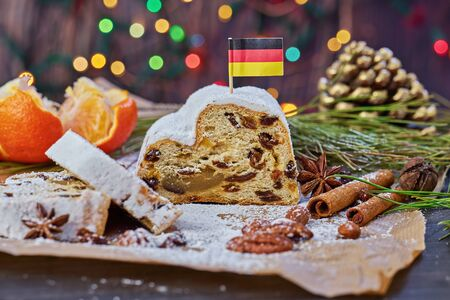 Christmas Stollen is traditional German sweet fruit loaf with icing sugar Xmas holiday table setting, decorated with garlands, nuts, and cinnamon sticks