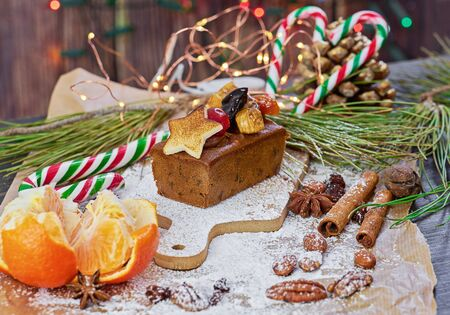 Christmas homemade gingerbread cake with sweet dried fruit with icing sugar Xmas holiday table setting, decorated with garlands, nuts, and cinnamon sticks Stock fotó