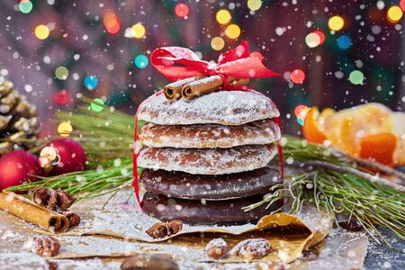 Stack of Christmas gingerbread rounds cookies tied with red ribbon icing sugar Xmas holiday table setting, decorated with garlands, nuts, and cinnamon sticks Stock fotó - 136788665