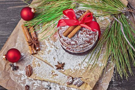 Top view of Christmas gingerbread roundscookies tied with red ribbon and icing sugar Xmas holiday table setting, decorated with garlands, nuts, and cinnamon sticks