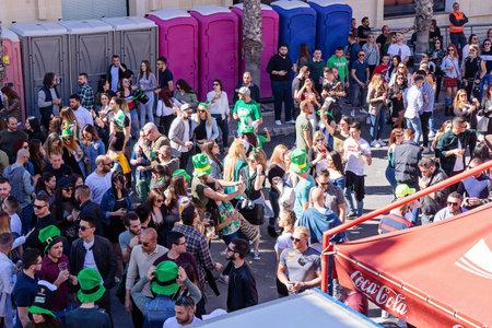 Above view of crowd of people dancing on street during celebration St. Patricks day in San Giljan, Malta. San Giljan, Malta - March 17, 2019 Editorial