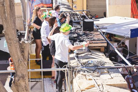 DJ and his team on outdoor stage entertain crowd of people dancing on street during celebration St. Patrick's day in San Giljan, Malta. San Giljan, Malta - March 17, 2019 Editorial