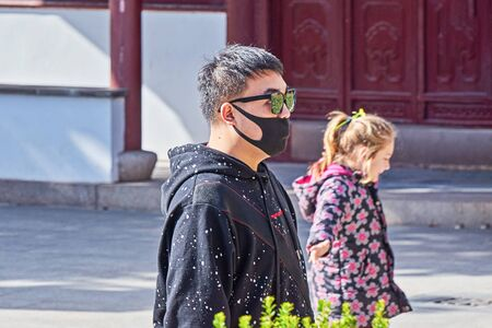 Asian man in medical mask on face in public place Garden of Serenity during celebration of Chinese New Year in Malta: Santa Lucija, Malta - January 19, 2020