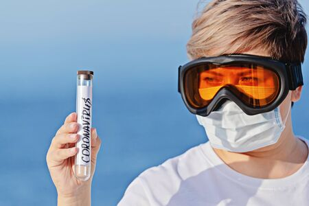 Woman in protective goggles and surgical mask holds hand abstract laboratory tube with coronavirus 2019-nCov. Concept of spread of Coronavirus 2019-nCoV virus around world