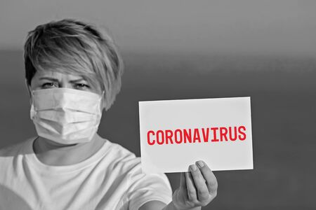 Woman in protective surgical mask holds blank with text coronavirus 2019-nCoV. Concept of spread of Chinese Coronavirus 2019-nCoV virus around world