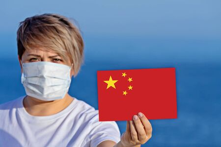 Woman in surgical face mask hold China flag. Outbreak of Wuhan coronavirus 2019-nCoV. Concept of spread of Chinese Coronavirus 2019-nCoV virus around world