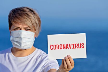 Woman in surgical face mask holds blank with text coronavirus 2019-nCoV. Concept of spread of Chinese Coronavirus 2019-nCoV virus around world
