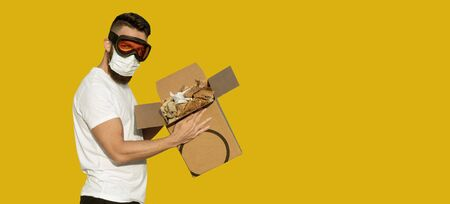 Unboxing of an infected postal package. Man in protective goggles and surgical mask unpacking infected cardboard box. Postal parcel may contain biohazard
