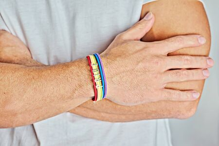 Closeup man with arms crossed in rainbow bracelet and text pride on white t-shirt. Happiness, freedom and LGBT concept