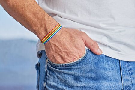 Male hand with rainbow bracelet and text pride in pocket of jeans. Happiness, freedom and LGBT concept