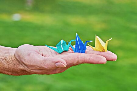 Traditional Japanese paper crane on male hand as symbol of peace and happiness on green background. Male palm with colorful handmade paper cranes orizuzu with copy space Stock fotó