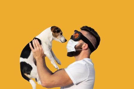 Caucasian bearded man in face mask and protective glasses holding up cute dog jack russell near face. Concept of pet allergy or dog smell in house