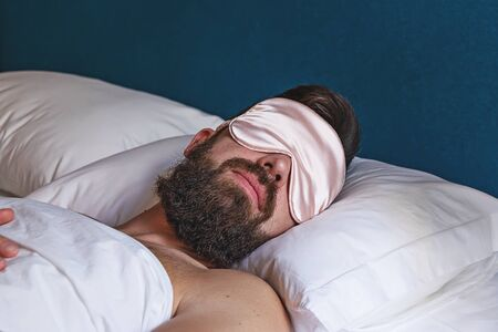 Closeup portrait of bearded man in eyemask sleeping in bed. Concept of sleeping mask help by insomnia or resting in travel Stock fotó