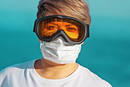 Woman in protective goggles and surgical face mask looking at camera. Stock fotó