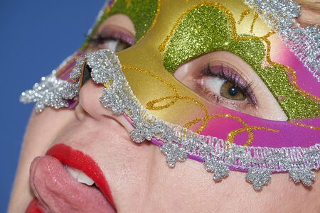 Closeup portrait of woman in Mardi gras masquerade mask in complementary art style. Funny face during celebration Mardi Gras. Flash photography, direct flash