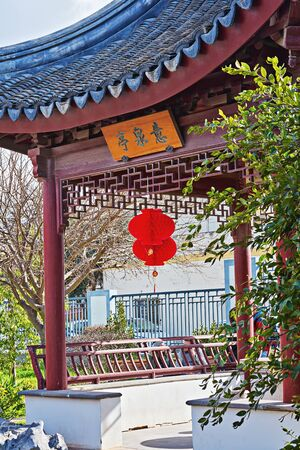Chinese gazebo in garden with Chinese red traditional lantern and sign with words Spirit. Meaning. Force. Traditional Chinese red lantern hanged in garden during celebrating Chinese New Year.