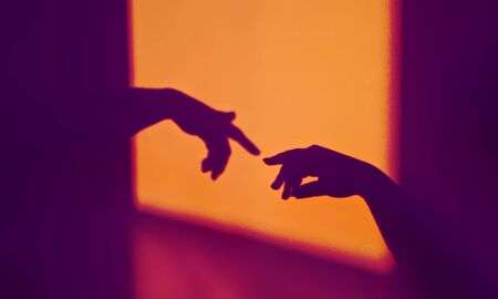 Abstract shadow silhouette of gesture touch by humans palms from sunbeam on wall during posing wrist and fingers in contrasting colors. Creation of Adam metaphor by Michelangelo Stock fotó