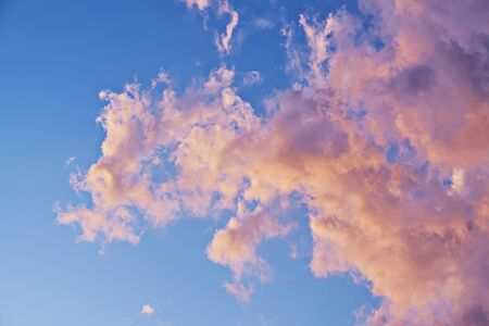 Pink and yellow pastel color clouds on blue sky in sunset light. Natural beautiful background of sky with copy space