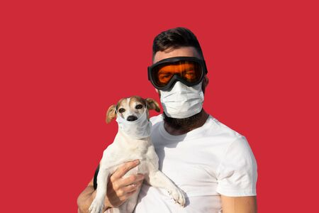 Man in protective mask and glasses holds cute jack russell dog in medical mask. Stock fotó