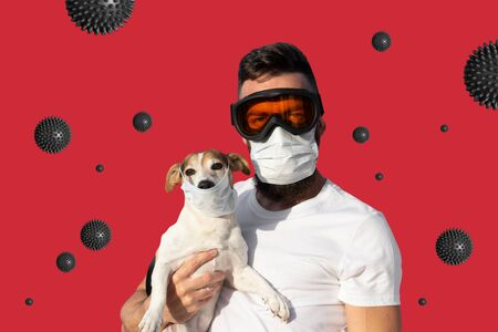 Man in protective mask and glasses holds cute jack russell dog in medical mask and abstract virus strain on red background. Stock fotó