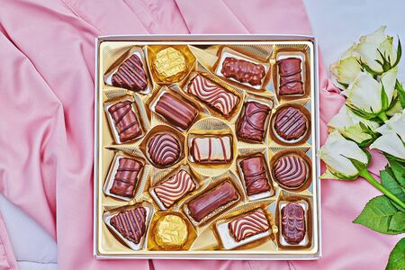 Golden gift box of assorted chocolate on pink silk background with white bouquet of rose. Greeting card to celebrate Valentines Day, Mother day or birthday Stock fotó