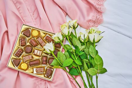 Golden gift box of assorted chocolate on pink lady satin kimono background with white bouquet of rose. Greeting card to celebrate Valentines Day, Mother day or birthday Stock fotó