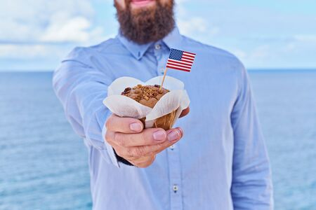 Headless man holds cupcake with miniature American flag USA. Greeting card for celebration of President's Day in America concept, Independence day, Flag Day USA, wide-angle effect