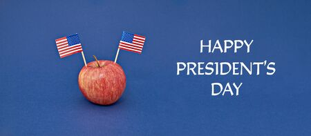 Happy Presidents day inscription on blue background with ripe red apple with two flag of USA, banner copy space