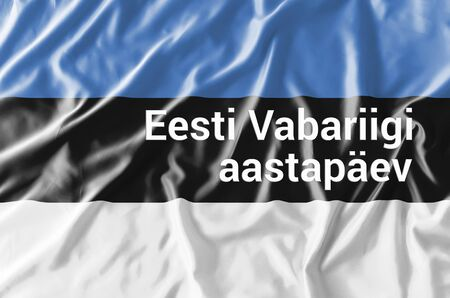 Waving Estonian flag with inscription in Estonian language Independence Day. Estonia celebrate annually on February 24 in honor of adoption of the Declaration of Estonian Independence in Tallinn