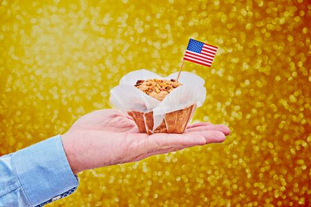 Cupcake with American flag on male palm against golden background with colorful bokeh to celebrate Presidents, Labor , Independence, Flag day, Veteran Day, Vote day
