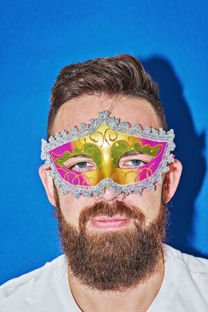 Closeup portrait of man in Mardi gras masquerade mask in complementary art. Funny face during celebration Mardi Gras, banner copy space Stock fotó