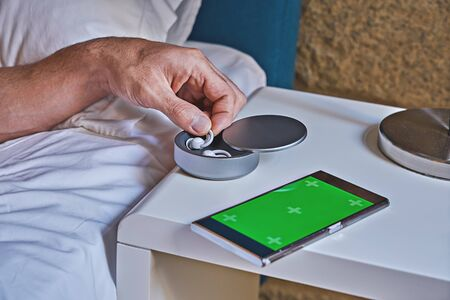 Man takes one of noise-masking sleep buds (sleepbuds) from holder on table. Modern technology gadget to improve quality of sleep concept Stock fotó