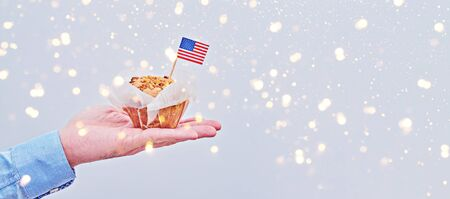 Cupcake with American flag on male palm against light background with colorful sparkles. Long banner with copy space to Presidents Day, Labor Day, Independence, Flag, Veteran Day, Vote